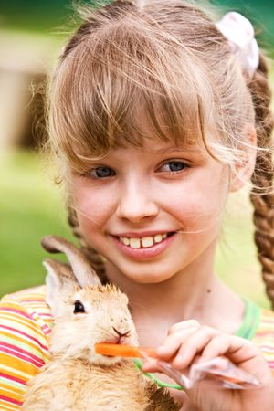 Happy girl feed rabbit with carrot. Outdoor. photo