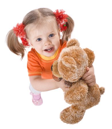 Child girl in orange with teddy bear in angle. photo