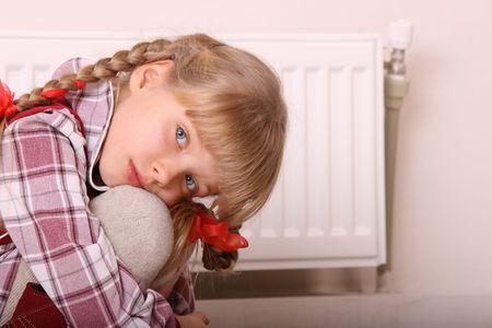 tress: Sad girl sitting near heater. Children depression.