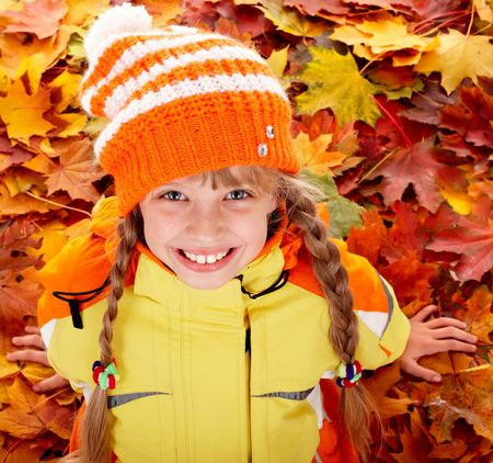 tress: Girl in autumn orange  hat on leaf background.Outdoor.