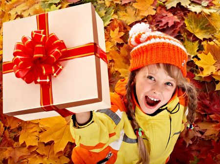 Girl in autumn orange  hat on leaf and gift box.Outdoor. photo