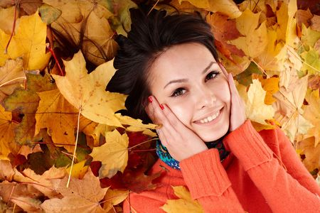 Girl in autumn orange hat on leaf group. Outdoor. photo