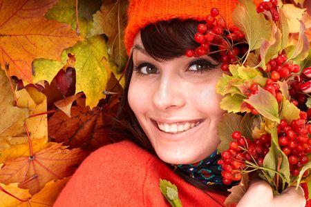 Girl in autumn orange hat on leaf group. Outdoor. photo