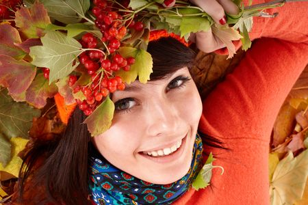 Girl in autumn orange hat on leaf group and berry. Outdoor. photo