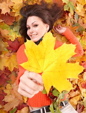 Girl in orange on autumn foliage with yellow leaf.  Outdoor. Stock Photo - 5722810