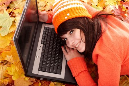 Girl in autumn orange leaves with laptop. Fall sale. Outdoor. photo