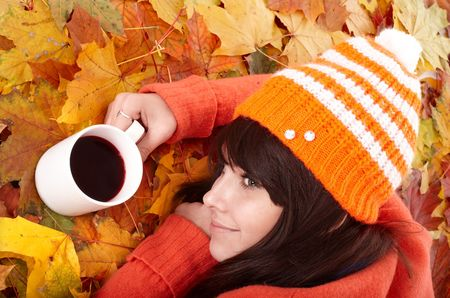 Girl in autumn orange leaves with cup coffe. Outdoor. Stock Photo - 5722096