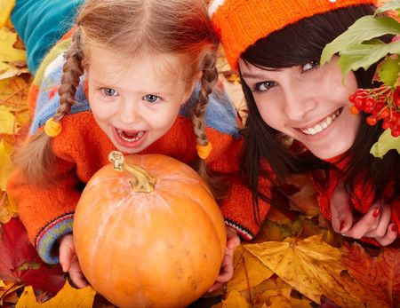 one family: Happy family with child on autumn orange leaf, pumpkin.Outdoor. Stock Photo
