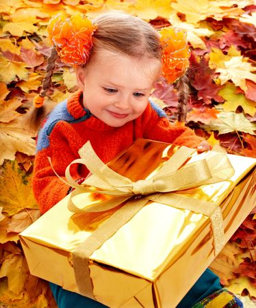 Girl in autumn orange hat on leaf and gift box. Outdoor. photo