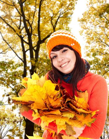 Girl in autumn orange hat with leaf group near tree.  Outdoor. photo