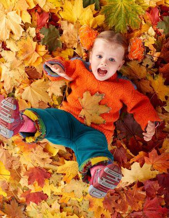 Girl child in autumn orange leaves. Outdoor. photo
