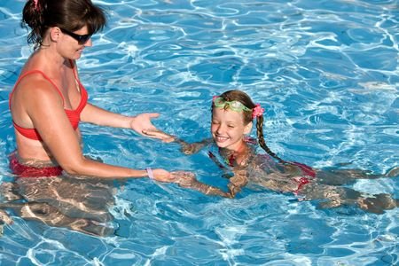 Instructor girl learn child swim in swimming pool. photo