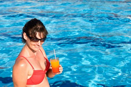 Girl in red bikini drink alcoholic cocktail in swimming pool. Stock Photo - 5775329