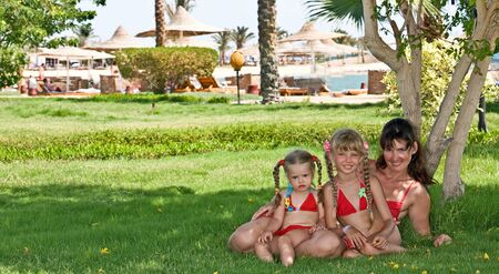 Happy family on green grass in park near beach.Outdoor. photo