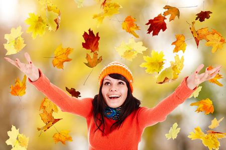 Girl in autumn orange hat with outstretched arm. Outdoor. photo