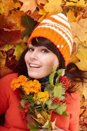 Girl in autumn orange hat on leaf group with flower. Outdoor. photo
