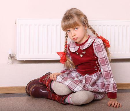 Girl  warm  near radiator.  Energy crisis. photo