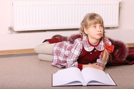 Girl lie near radiator with book. Cold crisis. Stock Photo - 5803559