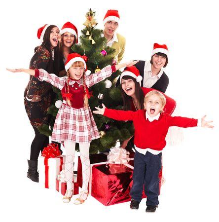 fiesta familiar: Grupo de personas, los ni�os en el sombrero de Pap� Noel, con �rbol de Navidad. Aislados. Foto de archivo