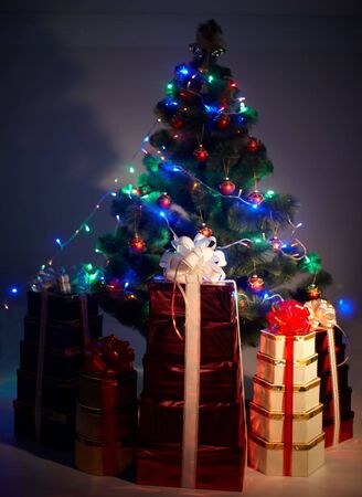 Christmas tree with flash and group gift box, shadow. Black background. photo