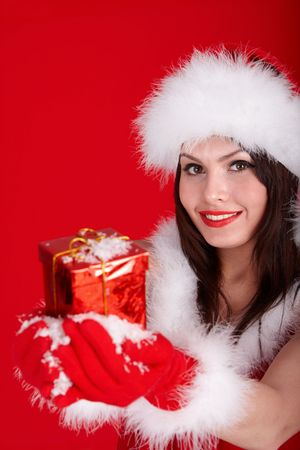 Christmas girl in santa hat with small red gift box,snow. Red background. photo