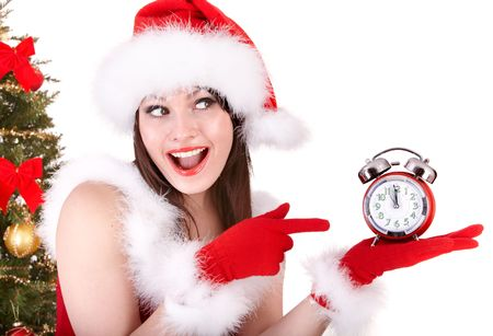 Christmas girl in santa hat and fir tree with alarm clock. Isolated. photo