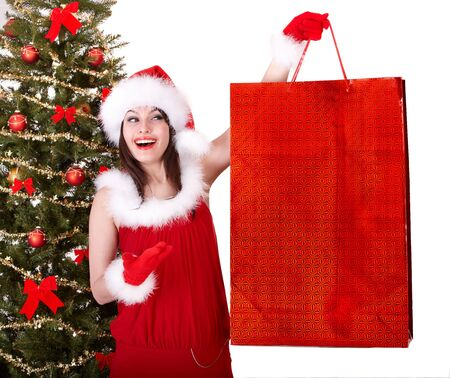 Christmas shopping of girl in santa hat and fir tree. Isolated. photo