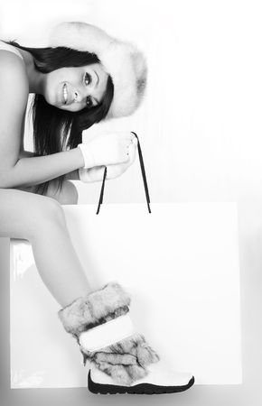 Girl in winter fur hat and shoes with shopping bag. Black and white image. photo