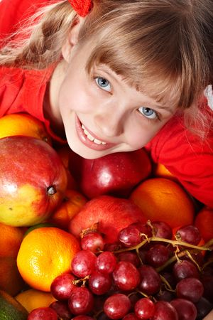 Child girl in group of fruit. Healthcare. photo