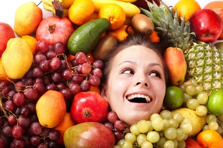 Happy girl in group of fruit. photo