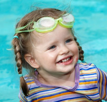 Child girl in protective goggles swimming pool. photo
