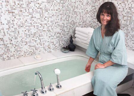 Young woman wearing green bathrobe in bathroom. photo