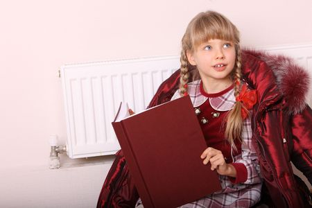 Girl lie near radiator with book. Cold crisis. Stock Photo - 6207252