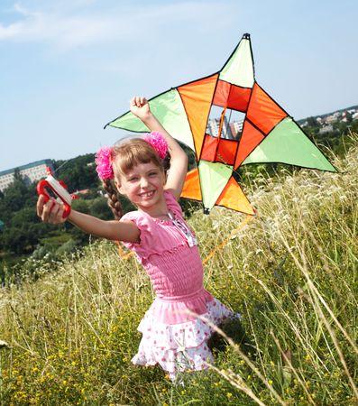 Girl in green grass fly kite. Summer. photo