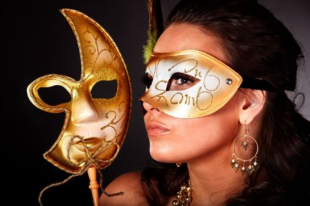 Beautiful young woman with gold mask on grey background. photo