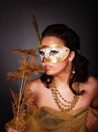 Beautiful young woman with gold mask and flower on grey background. photo