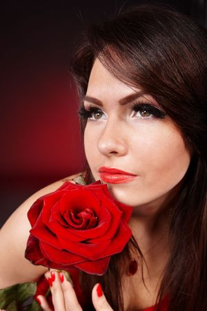 Girl with rose on red background. Valentines day. photo