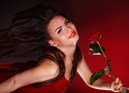 Girl with red flower rose  running. Valentines day. photo