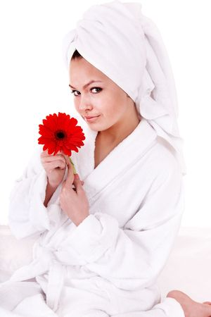 Beautiful young woman with red flower in spa. Isolated. photo