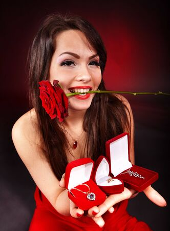 Girl with group jewellery gift box and rose on red  background.   Valentines day. photo