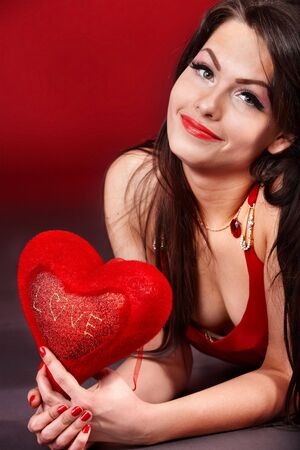 Girl with  heart  on red  background.  Valentines day. photo