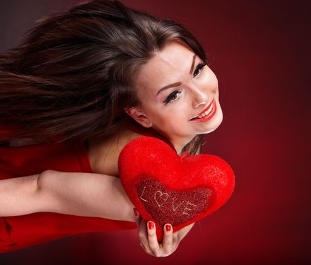 Girl with heart on red background flying. Valentines day. photo