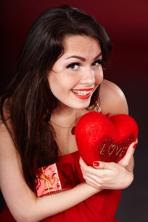 Girl with  heart  and gift box on red  background.   Valentines day. photo