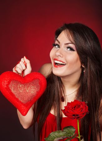 Girl with  heart and flower rose on red  background.  Valentines day. photo