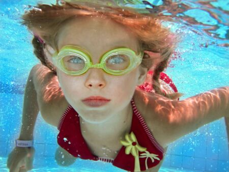 lesson:  Child girl swim underwater in pool. Sport lesson.