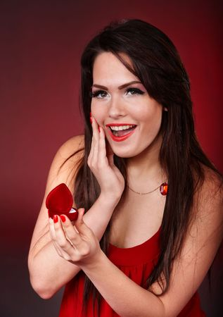 Girl with jewellery gift box on red background. Valentines day. photo