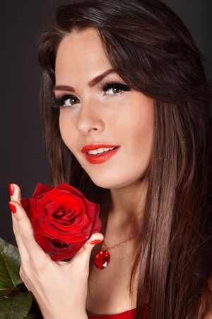 Girl with flower rose on red background. Valentines day. photo