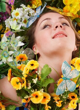 Beautiful girl with butterfly and flower on grass. Outdoor. photo