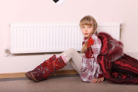 Girl in coat warm  near radiator.  Energy crisis. Stock Photo - 6395742