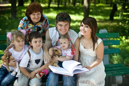 upbringing: Happy family with  child and grangmother in outdoor read book. Upbringing. Stock Photo